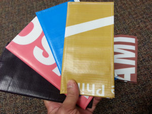 travel wallets made from discarded billboards