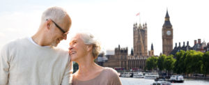 Couple with travel insurance for those over 65 standing on bridge with big ben in the background